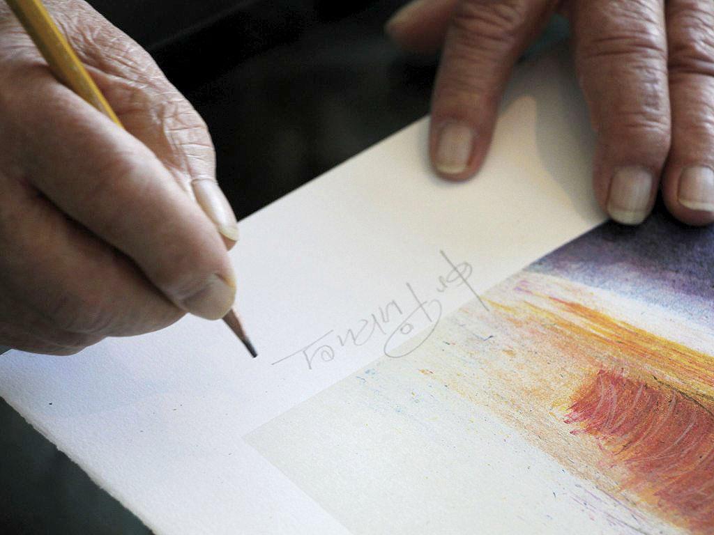 """Jos Pirkner signiert die Afralithographie """"Drei Frauen"""". (Foto: Knut Kuckel)"""