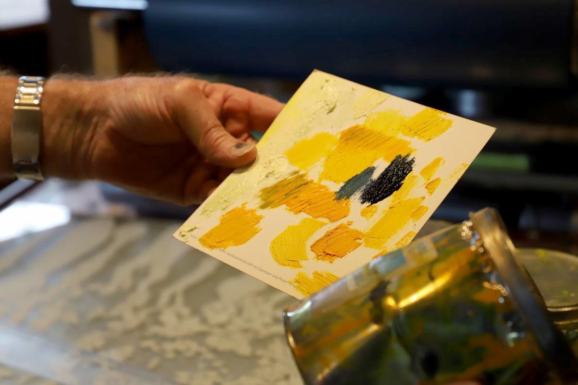 Der Steindrucker hält jetzt eine Palette mit Ölfarben in seiner Hand. Die Grundtöne sind überwiegend gelb. Foto: Knut Kuckel